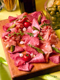 Plate with salami and bacon. Decorate with onion, gherkin  and tomato cherry Stock Photo