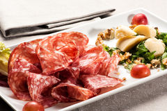 Plate of salami pieces beside parmesean cheese Stock Image