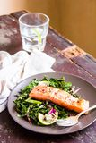 Plate of salmon fillet steak roasted with spices served with fresh salad with lime fruit and peppercorns on a wooden table, select royalty free stock photos