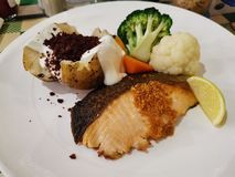 A plate of Salmon steak with baked potato and broccoli. Food, meal, dish, fish, fried stock images