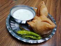 Plate of Samosa. A click of served plate of samosas seasoned with curd chutney and chillies stock image