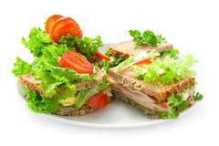 Plate with sandwiches. White plate with fresh colorful sandwiches with ham, cheese lettuce leaves and tomatoes Stock Image