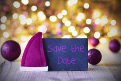 Plate, Santa Hat, Lights, Text Save The Date. Plate With English Text Save The Date. Purple Christmas Ball Ornaments And Santa Claus Hat. Wooden Background With Royalty Free Stock Image