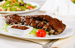Plate of Saucy Barbecue Pork Ribs in Restaurant Stock Photos