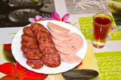 A plate with a sausage cut and a glass of wine. Homemade. A real, not staged photo royalty free stock image