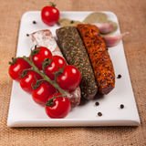 Plate with sausages and tomatoes. Plate with sausages, tomatoes, garlic, pepper and laurel leaves on a woven tablecloth Royalty Free Stock Photo