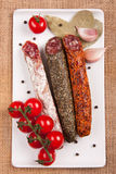 Plate with sausages and tomatoes. Plate with sausages, tomatoes, garlic, pepper and laurel leaves on a woven tablecloth stock image