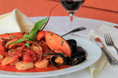 Plate of Seafood Fradiavolo with glass of red wine. White dinner plate with seafood fradiavolo  which includes tender shrimp,lobster and mussels simmered in a Stock Images