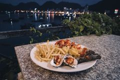 plate with seafood, mussels, shrimp, fish, octopus and French fries on the table against the sea at night outdoors. Vietnam ha stock photos