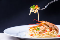 Plate with seafood spaghetti and pasta on fork. Royalty Free Stock Images