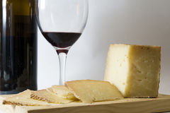Plate with a serving of cheese with a glass of red Stock Photos