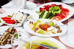 A plate with a set of different cheeses: Mazda, Parmesan, Blue Cheese, served with fruits. stock photos