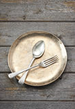 Plate Setting Wood Background. A gold plate with fork and spoon on a wood background Royalty Free Stock Images