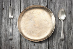 Plate Setting Wood Background. A gold plate with fork and spoon on a wood background Royalty Free Stock Photo