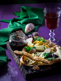 Plate with several types of cheese,sauce and red wine on violet table. Dark tones, selective focus. Stock Photos