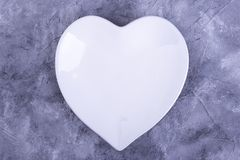 Plate in the shape of heart flat lay. Plate-heart on a gray background. Preparing for Valentine`s Day supper royalty free stock image