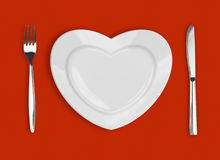 Plate in shape of heart, table knife and fork. On red background Royalty Free Stock Image