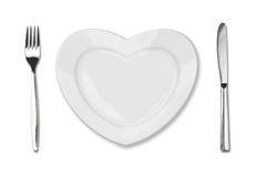 Plate in shape of heart, table knife and fork Stock Images