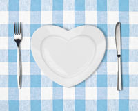 Plate in shape of heart, table knife and fork on blue tablecloth stock image
