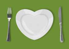 Plate in shape of heart, table knife and fork on green background royalty free illustration