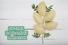 Plate with shekerbura and pakhlava as Novruz Holiday. Celebration on background with wordings Novruz Bayraminiz Mubarak stock photo