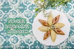 Plate with shekerbura and pakhlava as Novruz Holiday. Celebration on background with wordings Novruz Bayraminiz Mubarak royalty free stock photography