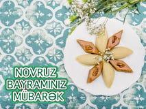 Plate with shekerbura and pakhlava as Novruz Holiday. Celebration on truqoise background with wordings Novruz Bayraminiz Mubarak royalty free stock image