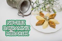 Plate with shekerbura and pakhlava as Novruz Holiday. Celebration on truqoise background with wordings Novruz Bayraminiz Mubarak stock photo