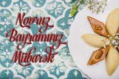 Plate with shekerbura and pakhlava as Novruz Holiday. Celebration on truqoise background with wordings Novruz Bayraminiz Mubarak stock photography