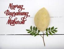 Plate with shekerbura and pakhlava as Novruz Holiday. Celebration on truqoise background with wordings Novruz Bayraminiz Mubarak royalty free stock photos