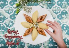 Plate with shekerbura and pakhlava as Novruz Holiday. Celebration on truqoise background with wordings Novruz Bayraminiz Mubarak stock image
