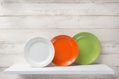 Plate at shelf on white wooden background Royalty Free Stock Photos