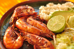 Plate of shrimp - mexican food. Plate of mexican food: shrimp, rice, avocado, lemon and lettuce on a hand-made plate Royalty Free Stock Photos