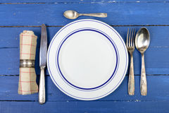 Plate with silver cutlery on an old table Royalty Free Stock Photography