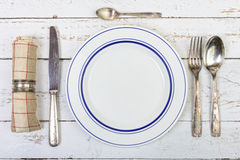 Plate with silver cutlery on an old  table Stock Image