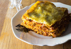 Plate of single serving of spicy beef lasagne for supper on rust. Ic wooden table stock photos