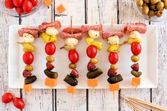 Plate of skewer appetizers overhead on white wood Stock Images