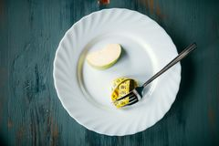 Plate with apple and measuring tape, weight loss. Plate with a slice of apple and measuring tape closeup. Weight loss diet concept Royalty Free Stock Photos