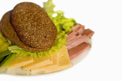 Plate with slice of ham and cheese. Bread, salad, ham, cheese and onion on the white background royalty free stock photography