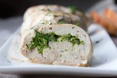 Plate of sliced chicken roll. Stuffed with baked green peas on sackcloth. Country style Stock Photos