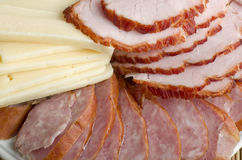 A plate of sliced ham, smoked sausage and cheese close-up. Royalty Free Stock Photography