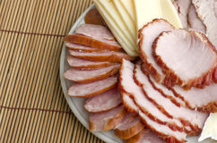 A plate of sliced ham, smoked sausage and cheese on table backgr Royalty Free Stock Photo