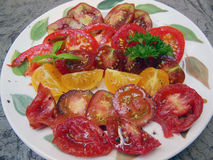 Plate of sliced heirloom tomatoes. Plate full of slices of heirloom tomatoes with olive, salt and pepper Royalty Free Stock Photo