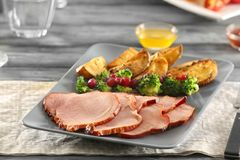 Plate with sliced honey baked ham and vegetables on table Royalty Free Stock Images
