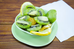 Plate with sliced kiwis lemons and oranges. On a wooden table stock image