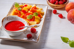 Plate of Sliced Peaches with Raspberry Sauce and Mint Leaf. Stock Images