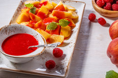 Plate of Sliced Peaches with Raspberry Sauce and Mint Leaf. Royalty Free Stock Images