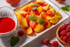 Plate of Sliced Peaches with Raspberry Sauce and Mint Leaf. Royalty Free Stock Photography