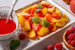 Plate of Sliced Peaches with Raspberry Sauce and Mint Leaf. Stock Image