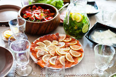 Plate with sliced salmon fish and salads on table Stock Image